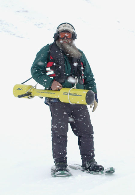 A man holding a Diver Held Magnetometer while snowing